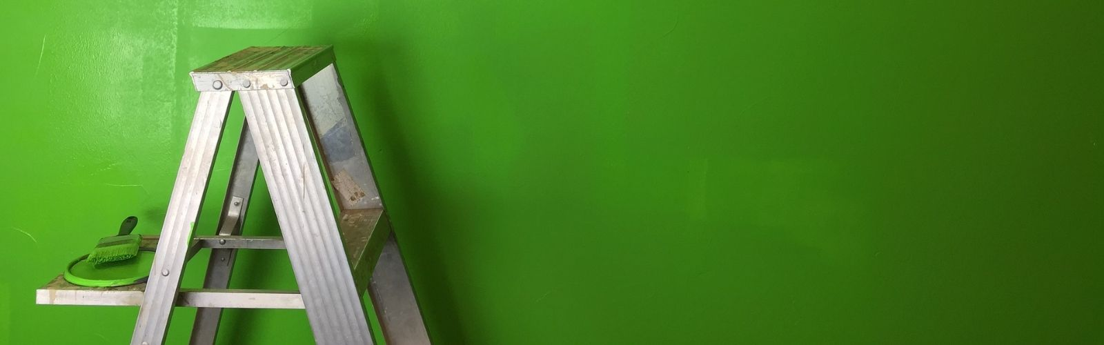a ladder in front of a green wall
